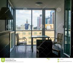 Table And Chairs In Apartment By Window Wall Looking Out On Skyline Of Brisbane Queensland Australia