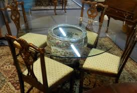 round transparent glass table on patterned acrylic base plus brown