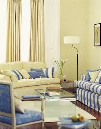 a pale butter yellow and cornflower blue living room with rich