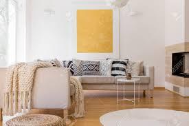großes goldgemälde auf weißer wand im einzigartigen wohnzimmer mit kamin und weißem teppich