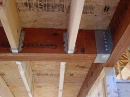 Lumber Floor Joists Are Supported By Joist Hangers Attached To An LVL Girder The Is In A Heavy Metal Hanger That Attaches Another