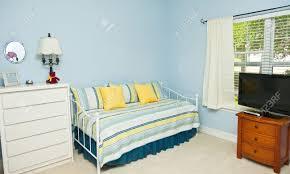 blau gefärbte wände in einem schlafzimmer mit schlafcouch tv und kommode