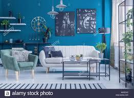 grün beige sofa und sessel gegen blaue wand mit schwarzen