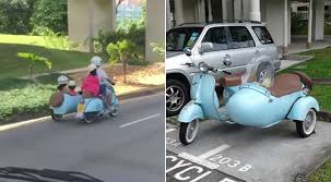 Family Of 4 Riding Vintage Vespa With Sidecar On Spore Road Is