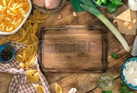 Empty Kitchen Board With Ingredients For Cooking A Delicious Pasta On Wooden Table Top