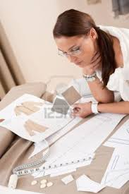 6046012 Female Fashion Designer Working With Sketches At