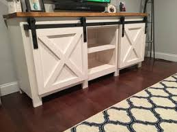 A TV Stand With Barn Doors And Shelves