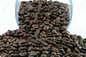 Many Coffee Beans On The White Background With Transparent Jar Stock Photo