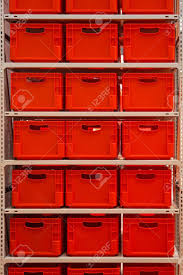 Shelf With Red Plastic Crates In Warehouse Stock Photo