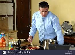 mann in hemd und krawatte in der kueche beim kochen kocht