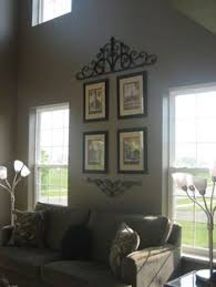 Two Story Living Room Three Candle Holders And Grouping Of Artwork To Take Your Eye Up