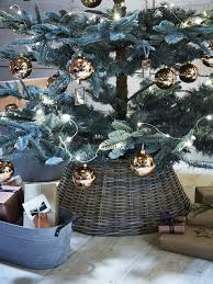 A Christmas Tree With Copper Ornaments And Basket That Hides The Base