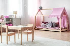 tisch und kleine stühle des kindes auf weißem teppich im skandinavischen artschlafzimmer mit holzmöbel