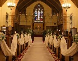 Church Altar Wedding Decorations Ideas With White Runners And Wooden Benches Also Flowers Under Two Chandeliers