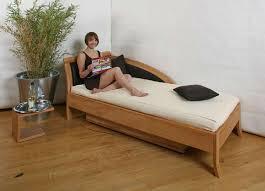 sofa und massivholzbett mit bettkasten in einem die möbelmacher