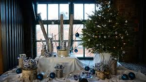 Using White Stippled Logs And Branches Of Silver Burch To Create Height The Display Glistens With Faux Snow A Christmas Tree Adorned Festive