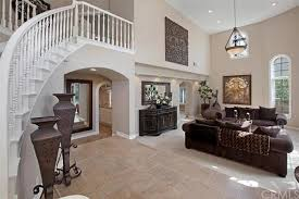 The Home Features A Two Storey Foyer With White Staircase