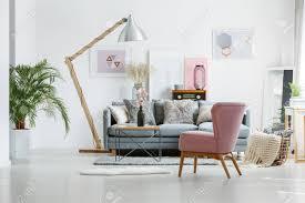 beige decke im korb auf dem boden im wohnzimmer mit rosa sessel und künstlerischen plakaten an der wand