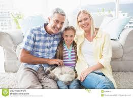 glückliche eltern und tochter mit kaninchen im wohnzimmer