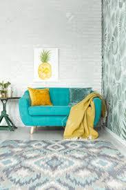 gelbe decke auf türkis sofa in hellen wohnzimmer mit ananas poster auf mauer
