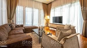 moderne innenarchitektur wohnzimmer mit braunen vintage sessel fernseher le große fenster und vorhänge stockfoto und mehr bilder alt