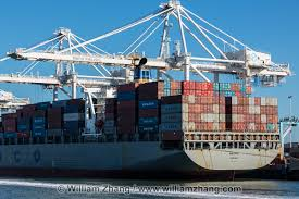 Cranes Shipping Containers And Freighter At Port Oakland CA