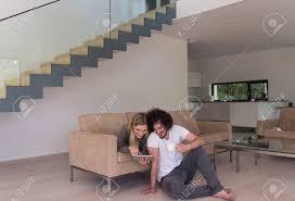 junges paar in luxuriösen haus mit tablet computern entspannt auf dem sofa im wohnzimmer zu lesen