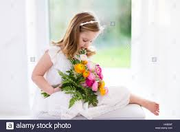 cute girl in white dress holding ranunculus flowers bouquet