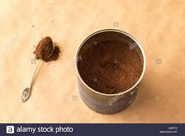 Container With Ground Coffee And A Spoon Powder On Brown Paper Background
