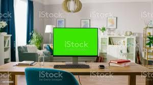moderne computer mit mockup greenscreendisplay steht auf dem schreibtisch des gemütlichen home office wohnzimmer des stilvollen interior designers