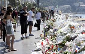 People Look At Flowers And Messages Placed Along The Beach Of Promenade Des Anglais In