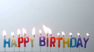 Colourful happy birthday candles being blown out in slow motion HD stock footage clip