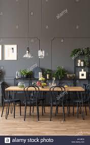 schwarze stühle an den hölzernen tisch in grau esszimmer
