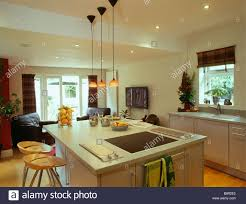 small orange pendant lights above island unit with fitted halogen