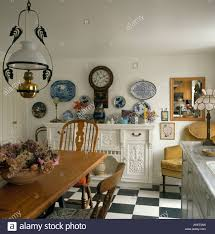Victorian Style Lamp Over Wooden Table In White Country Dining Room With Clock On Wall Above Sideboard