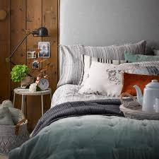 Cabin Style Country Bedroom With Plank Panelled Walls And Green Silver Linens