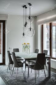 zimmer mit hellen wänden auf dem boden gibt es grauen fliesen und einem grauen teppich auf dem teppich steht tisch mit milchglasplatte und