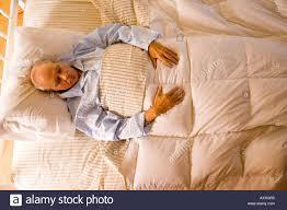 elderly man sleeping in his pajamas in his bed at home he sleeps