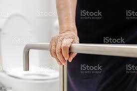 ältere frau hält am handlauf im badezimmer stockfoto und mehr bilder 70 79 jahre