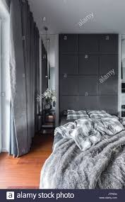 grau schlafzimmer mit doppelbett gepolsterte wand und