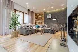 beige wohnzimmer mit einem großen ecksofa und einem designer stehle