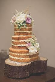 Naked Wedding Cake With Fresh Flowers On Log Slice