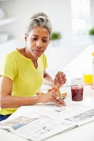 Une Femme Afro Américaine En Lisant Le Journal Femme Mûre Mangeant Le Petit Déjeuner Et Lisant Le Journal Image