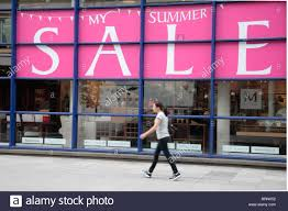 Woman Walking Past A Massive Summer Sale Sign At Multiyork Master Furniture Makers On Tottenham Court Rd London UK July 2010
