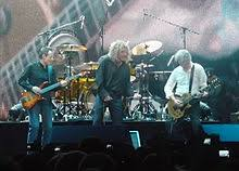 A Colour Photograph Of John Paul Jones Robert Plant And Jimmy Page Performing On Stage Led Zeppelin