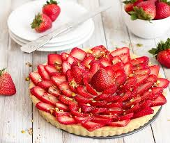 strawberry tart on a white wooden table with plates and a bowl of fresh strawberries in