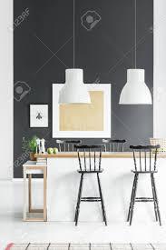 weiße len über küchenzeile mit rustikalen barhockern im esszimmer mit pflanzen