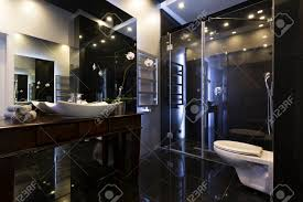 luxuriöses badezimmer mit dusche und dunklen fliesen