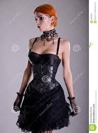 pretty redhead young woman in silver corset and black skirt stock