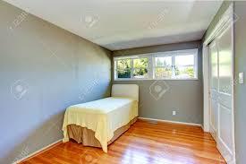 leeres kleines schlafzimmer mit parkett und grauen wänden ansicht der einzigen alten bett
